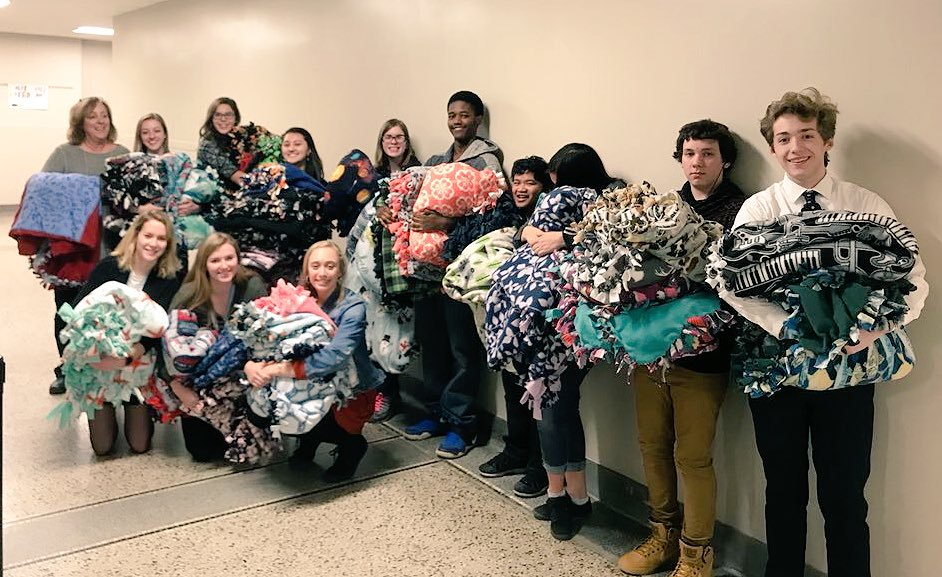 Cindy Widmar (far left) and members of the 2017 StuCo and IJag classes hold some of the blankets made for Covers of Comfort