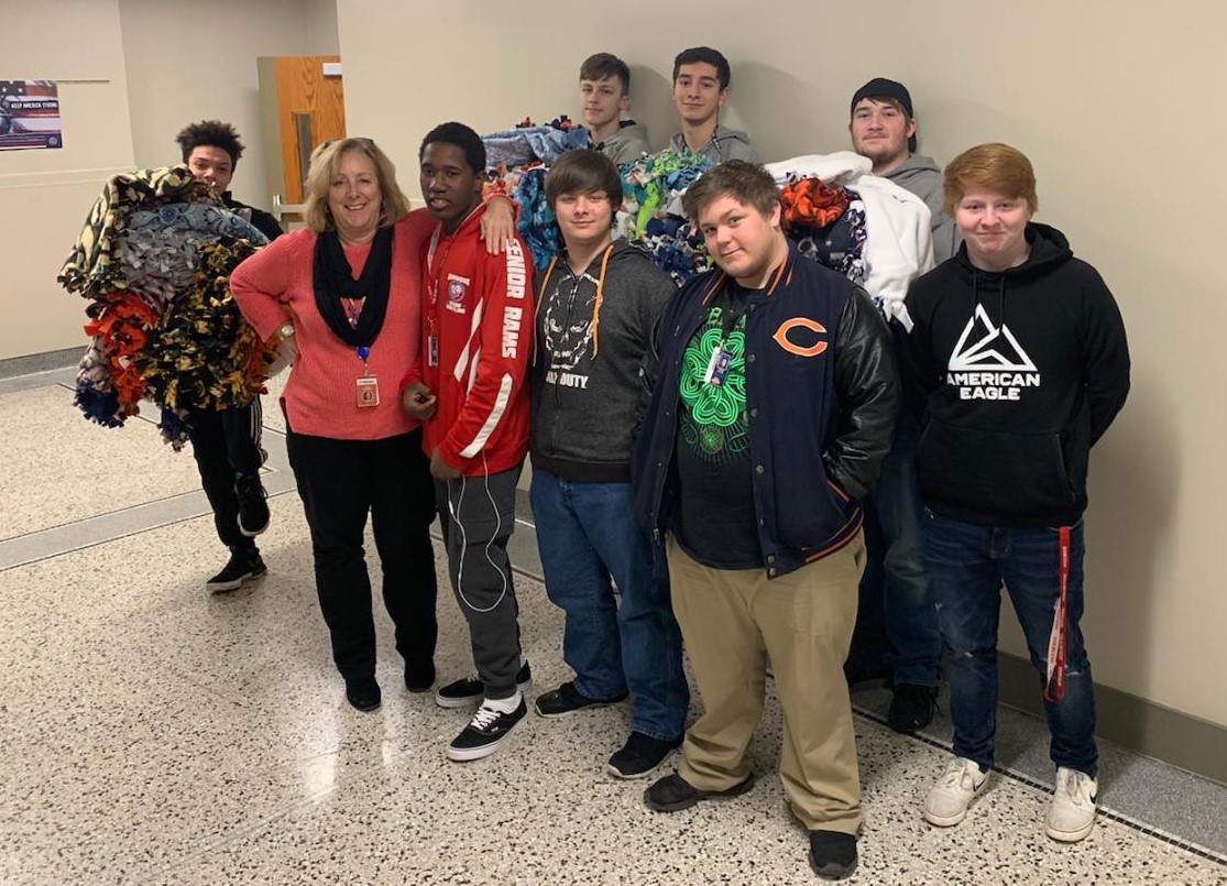 Cindy Widmar stands with some of the IJAG students who helped cut the material and tie the blankets  Front: DJ Hoskins (11), Cindy Widmar, DaShawn Tigges (11), Tristen Tison (11), and Chris Allen (11)  Back: Will McDonnell (11), Josh Weipert (11), Gage Boland (11), and Paul Breson (11)