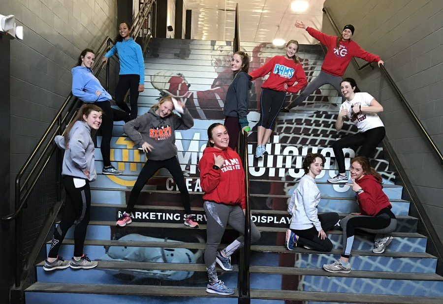 The distance running crew takes a stretch break at the Mystique Community Ice Center
