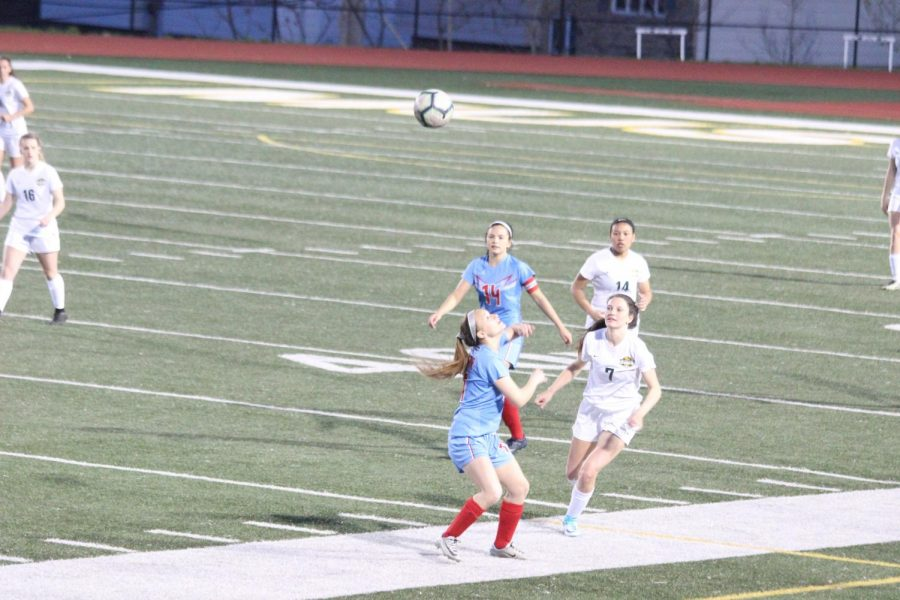 Maddie Barbee (11) goes for a header as Tia Martin (12) provides defense in their game against Hempstead
