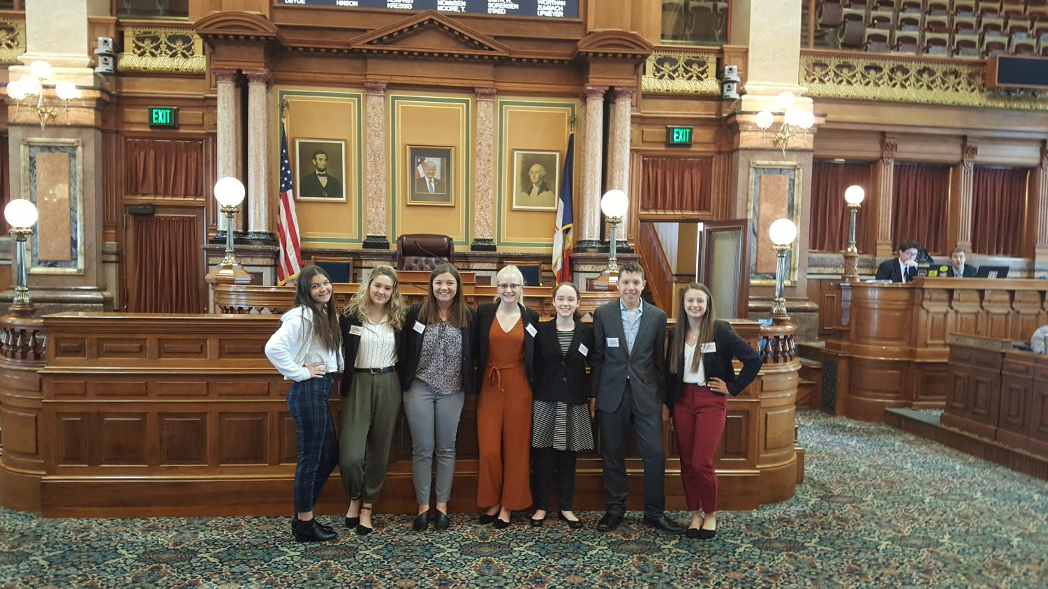 Model UN Delegates Bella Nekvinda (12), Tressa Weimerskitch (12), Alyssa Ernst (11), Emma Kalb (11), Madilyn Deifell (9), AJ Murdah (9), and Jillian Manternach (11) gather for a photo at the House Chamber of the Iowa Capitol Building.